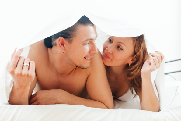 Loving middle-aged guy and woman  together under sheet on bed